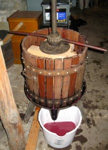 A think wooden disc, cut in half, is placed over the mushy grape remnants. The boards are placed ontop, and finally a metal disk and a metal bar that is turned to clamp down and press the grapes.