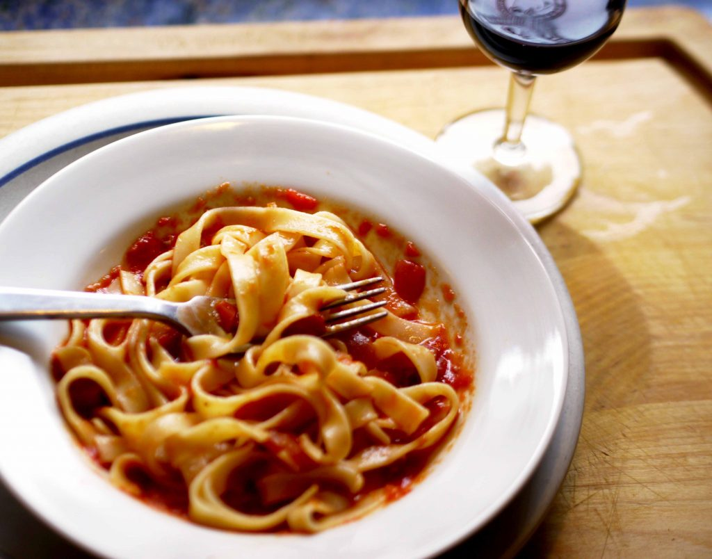 A bowl of pasta and a glass of red wine
