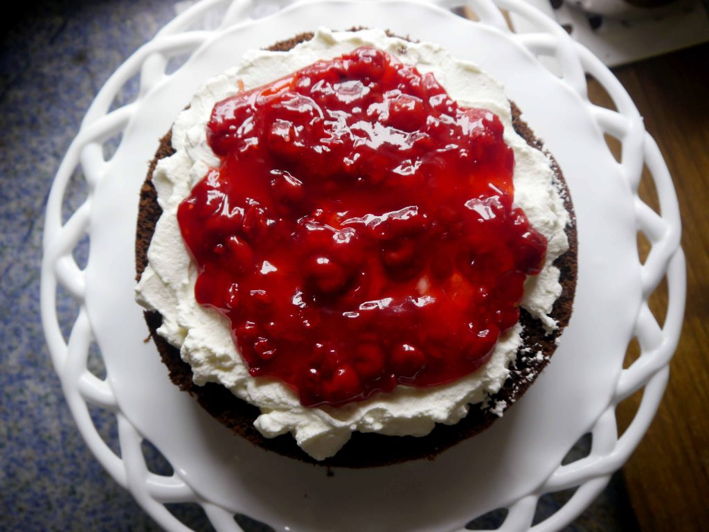 Cherry filling on top of whipped cream on top of chocolate cake.