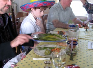 "Dan helps himself to some ""Simple Asparagus."" On Easter Sunday guests are asked to show up to dinner wearing their Easter bonnets and Gabriel complied with a sombrero.."