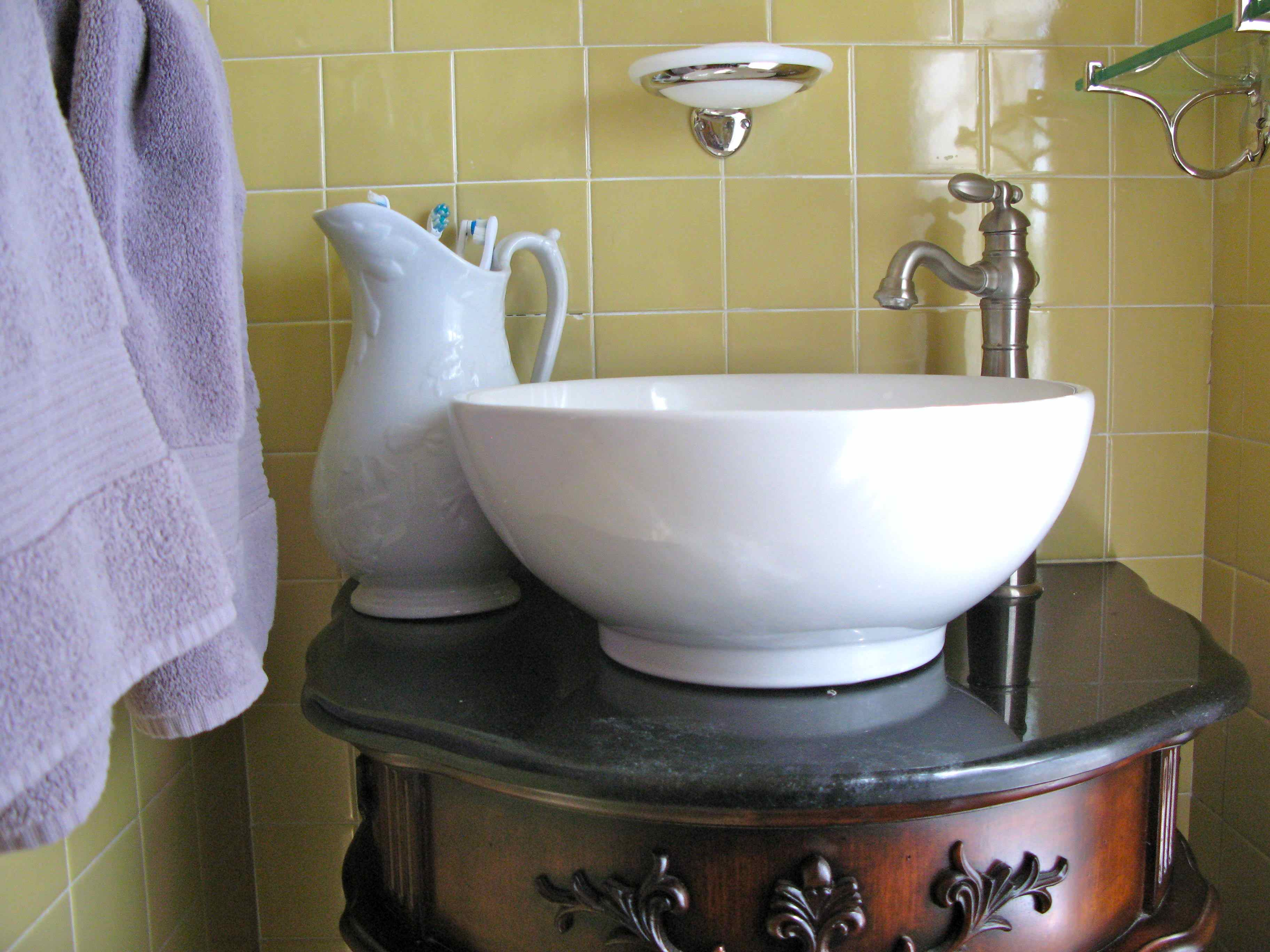 An antique pitcher was placed strategically next to the vessel sink to give the appearance of an old-fashioned wash basin and pitcher set. It's also a great place to store toothbrushes.