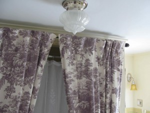 The acorn shade on the ceiling light works well with the romantic mood set by the toile shower curtain.