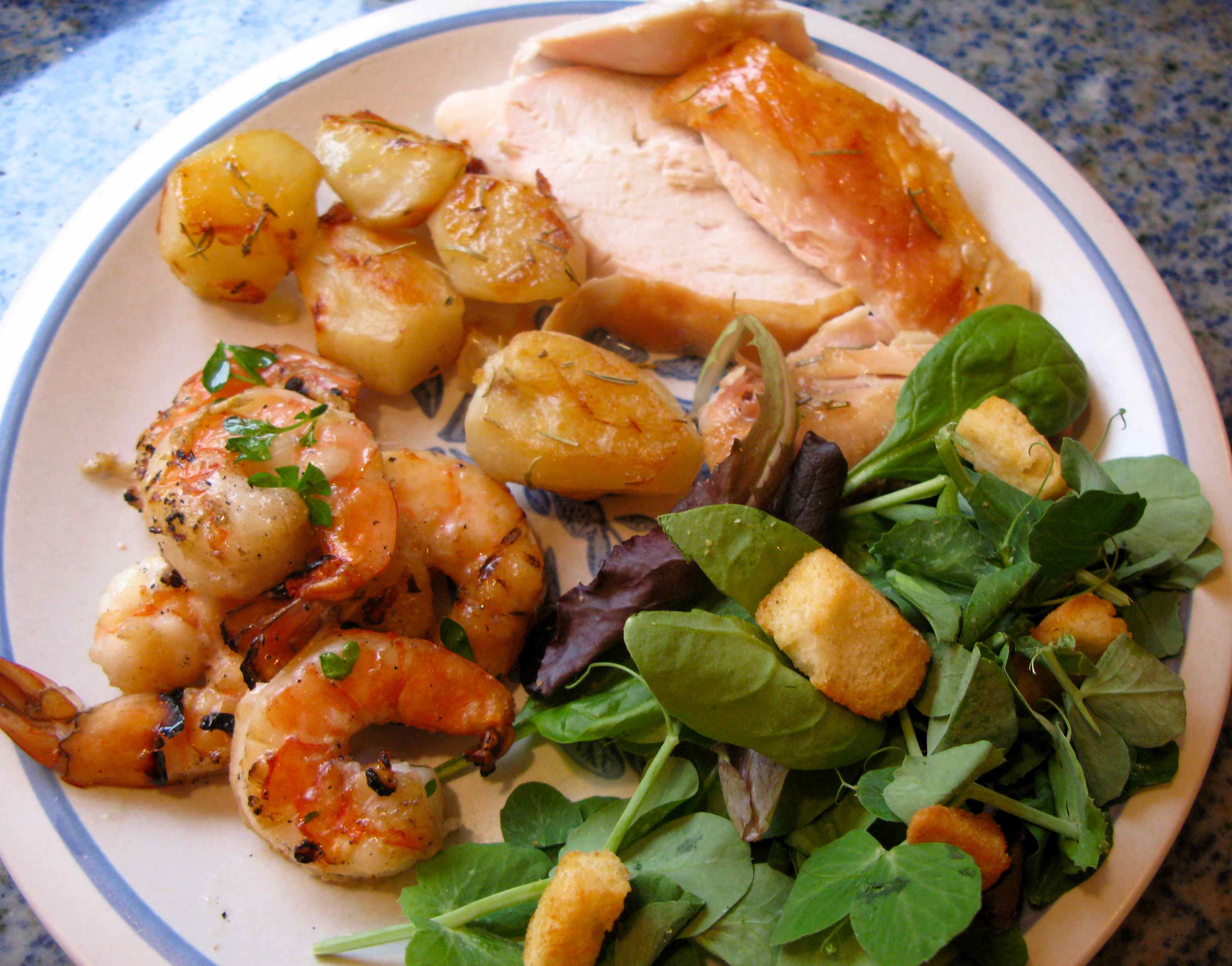 The combination of roasted chicken, barbecued shrimp, roast potatoes and fresh salad sends this dinner over the edge.