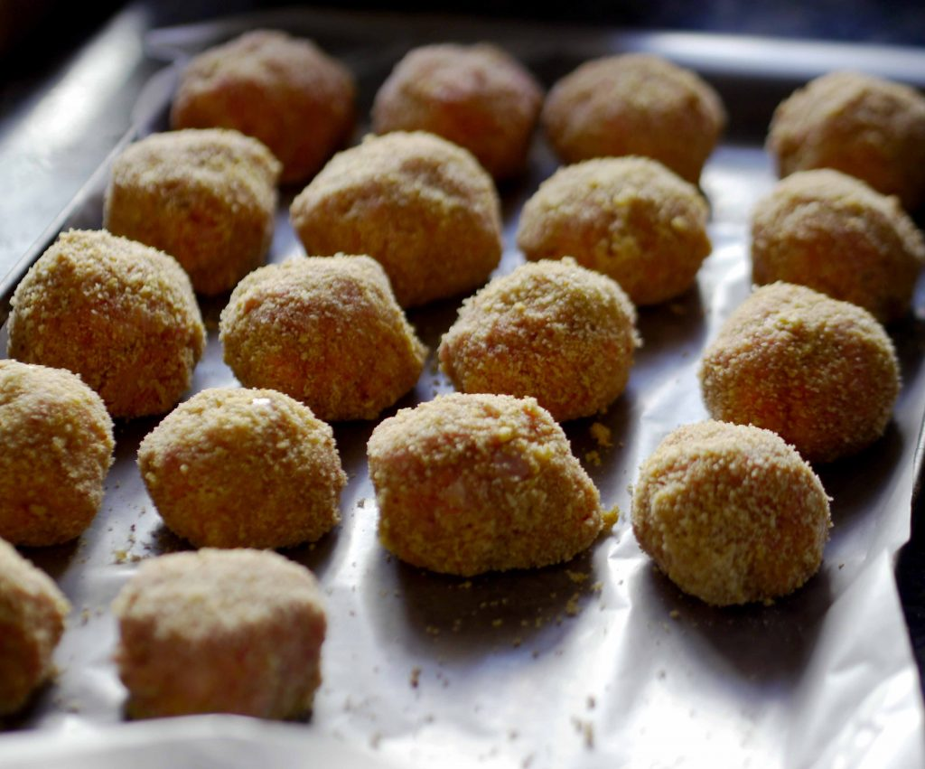 Uncooked meatballs on a cookie sheet