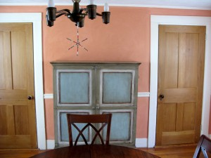 AFTER: The new dining room with the antique cabinet, painted walls, and bare wooden doors.