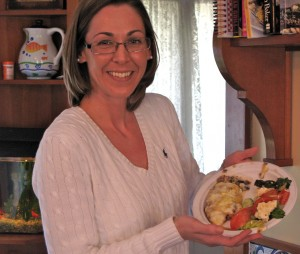 Maggie holds a plate of Moussaka and Greek salad.