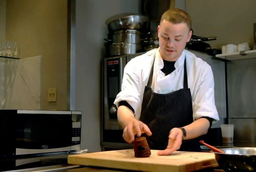 Chef Stephen Oxaal unveils a chocolate cake from a coffee cup