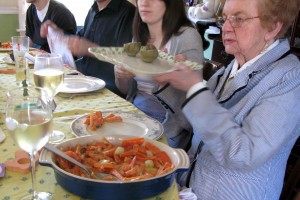 A woman passes a plate at a dinner table