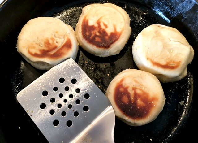English muffins cooking in a black skillet