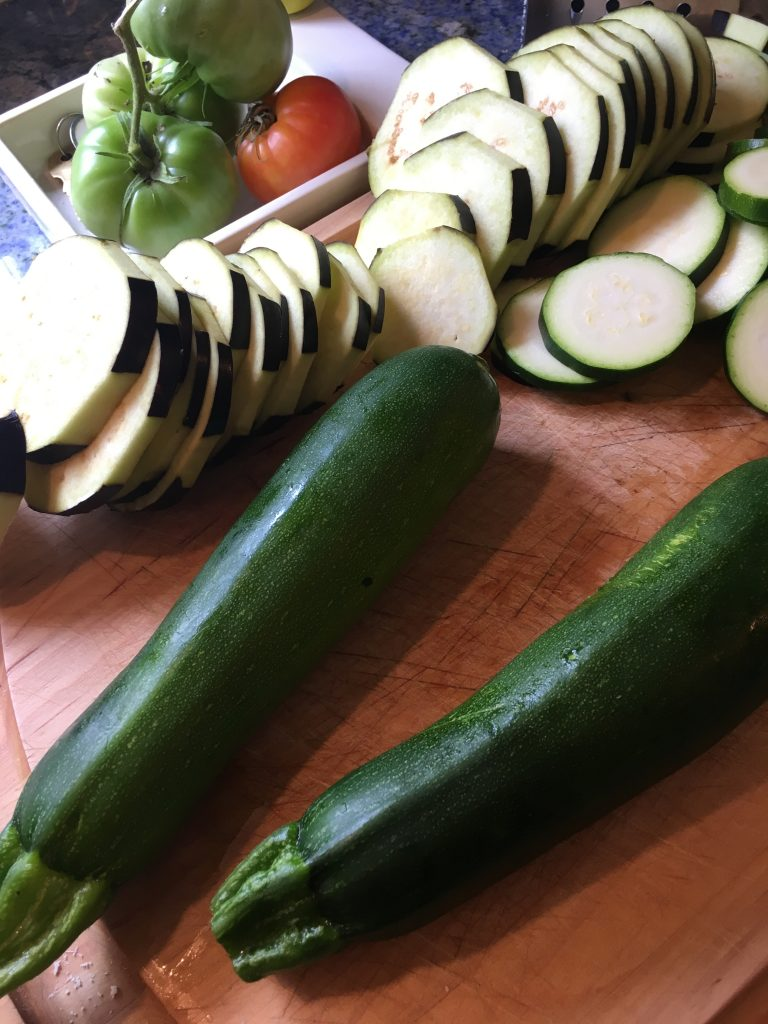 Zucchini on a cutting board with eggplant slices