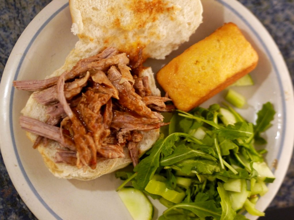 Pulled pork sandwich with corn bread and salad