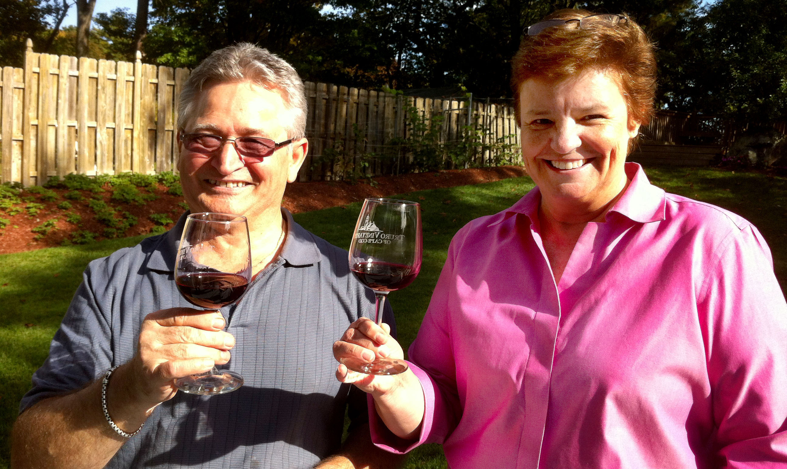 A man and a woman holding glasses of wine