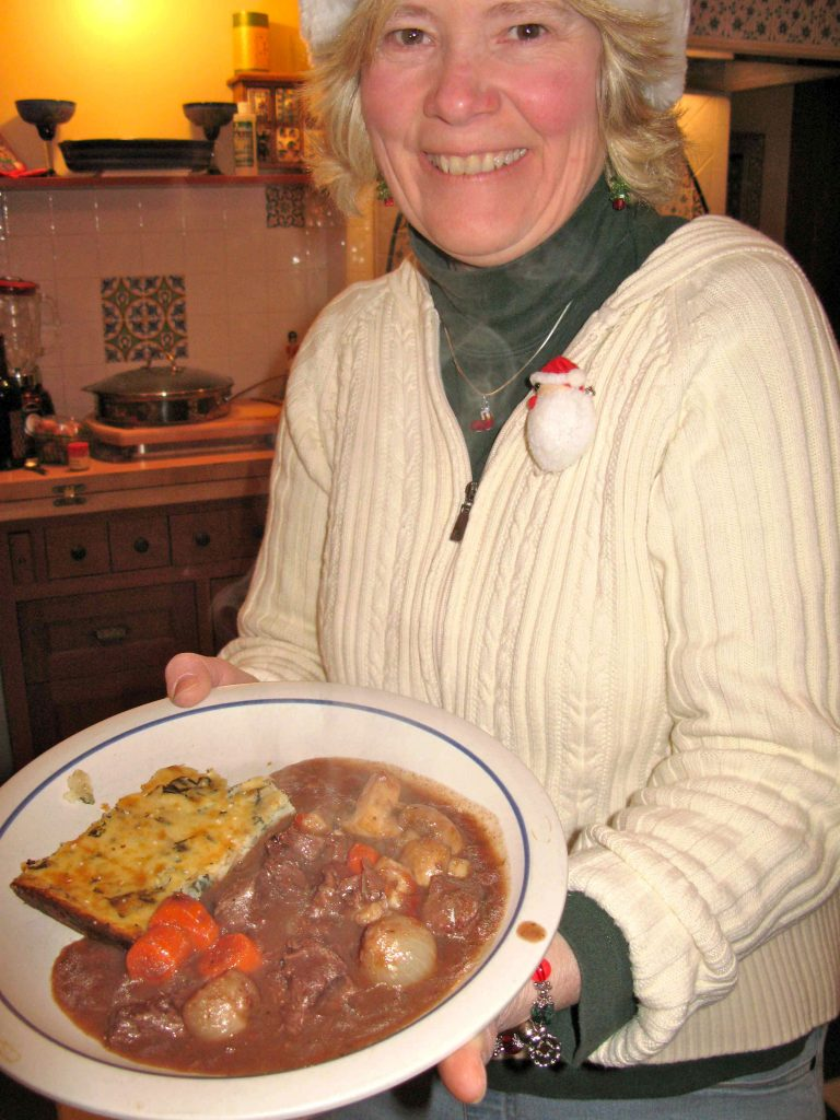 Tricia holding a plate of beef stew