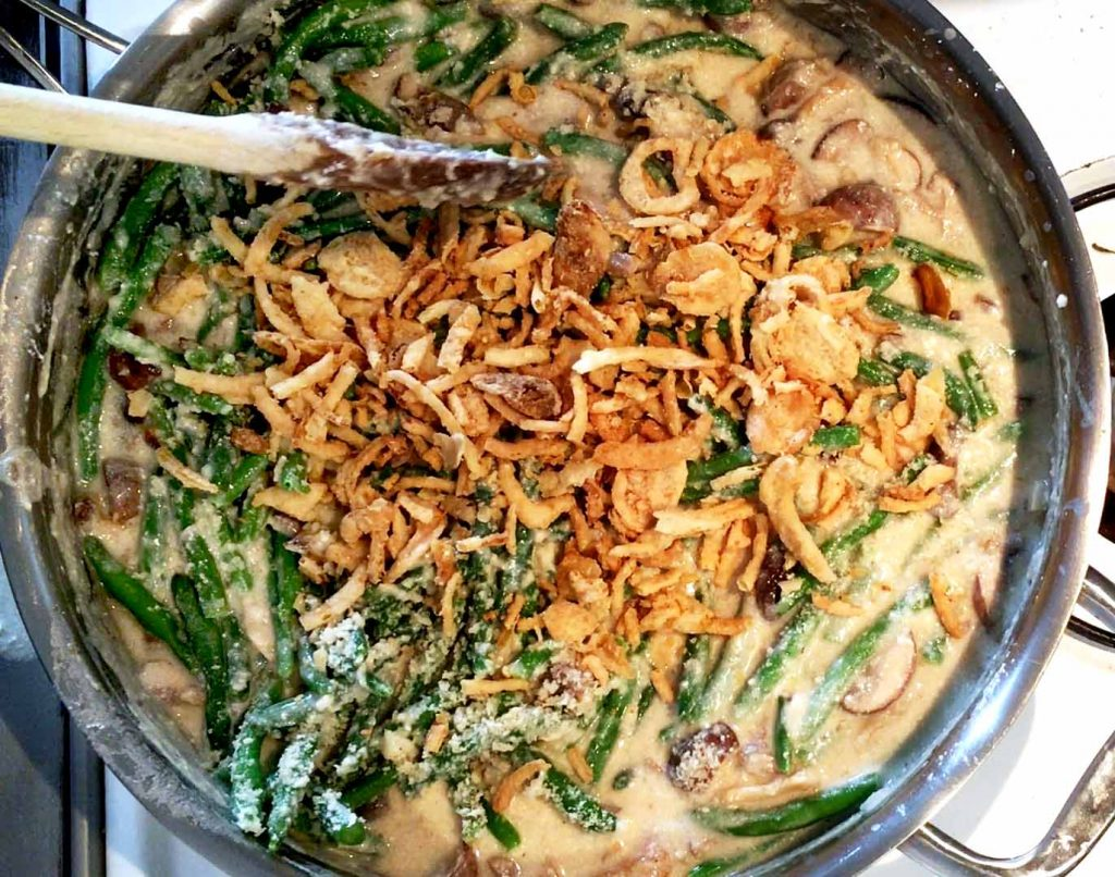 Green beans and fried onions on top of mushroom sauce in a frying pan
