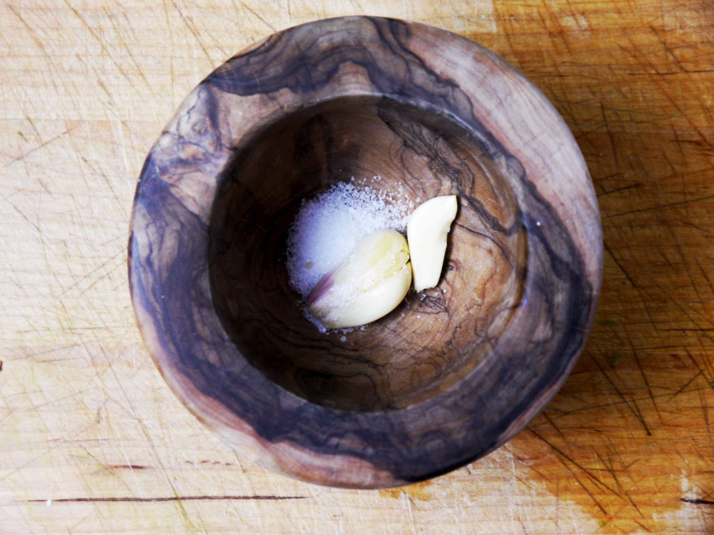 Garlic and salt in a wooden bowl.