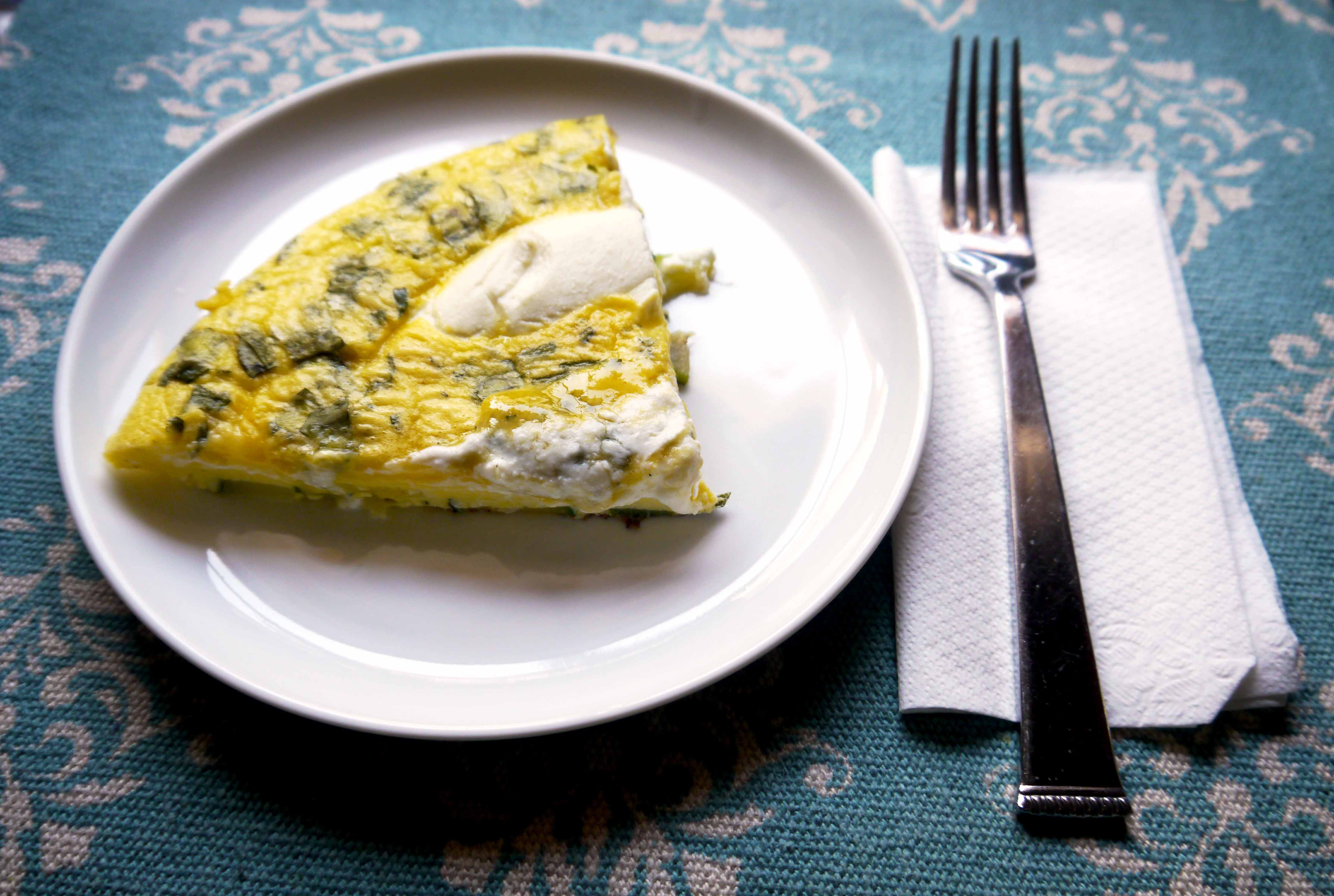 A slice of frittata on a plate.