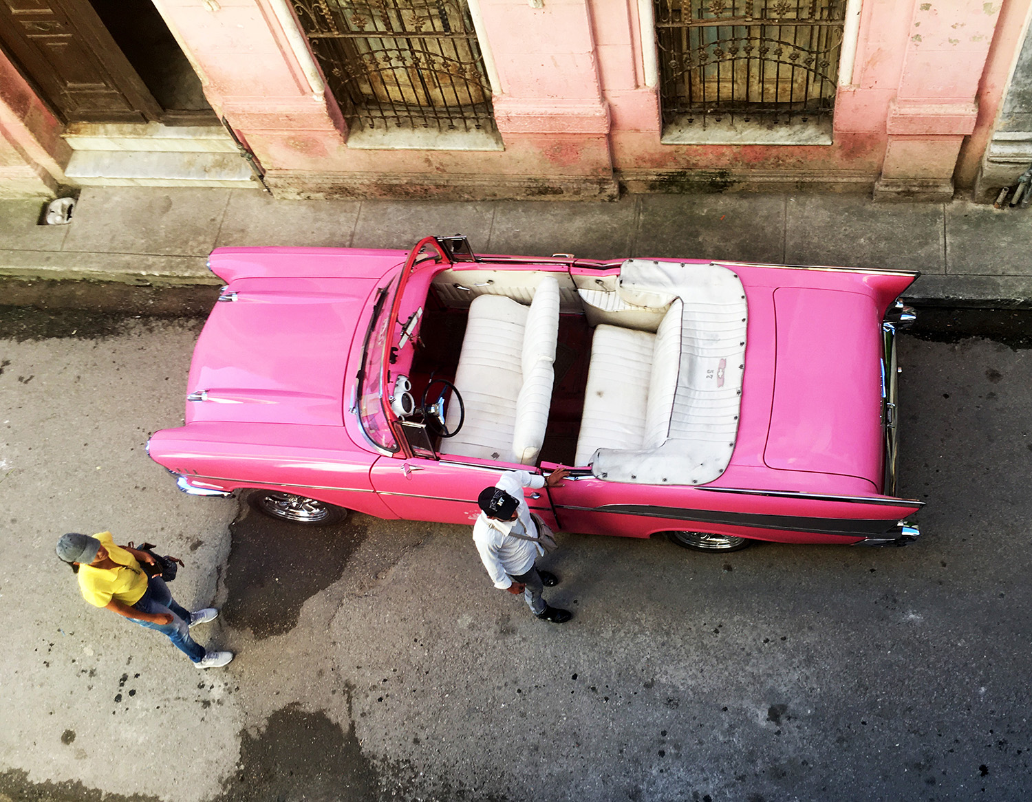 An aerial view of an old pink Impala.