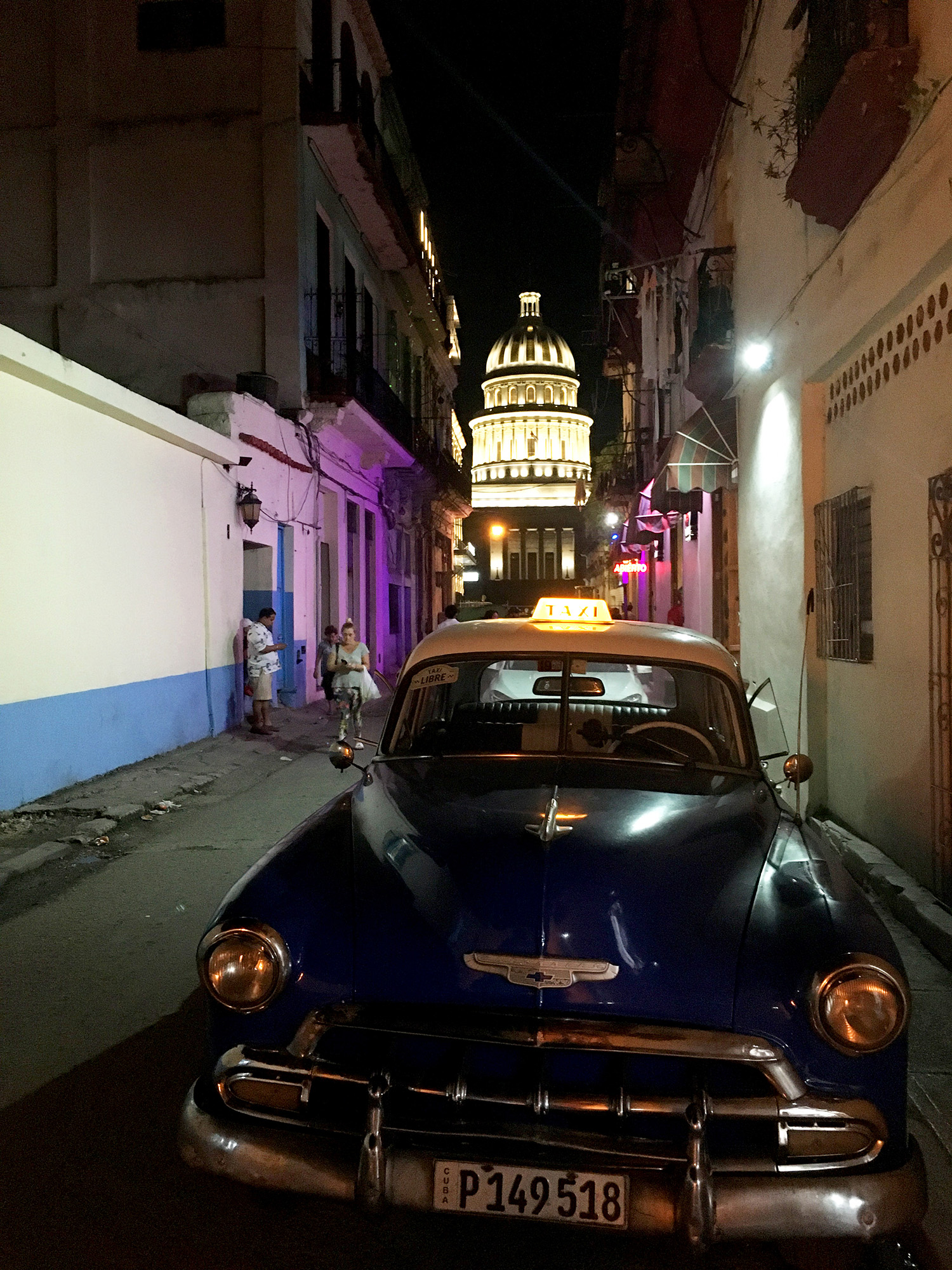 The light from El Capitolio shines on a 1950s car in Havana.