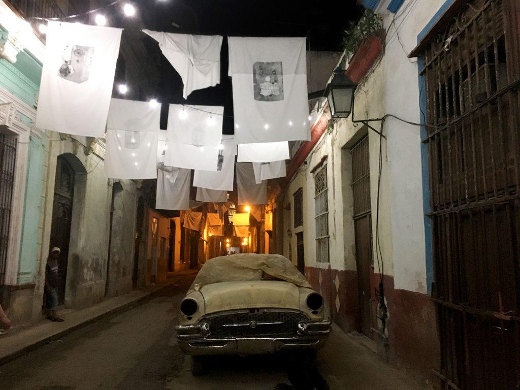1950s car on a dark street beneath a hanging cloth art exhibit in Old Havana.
