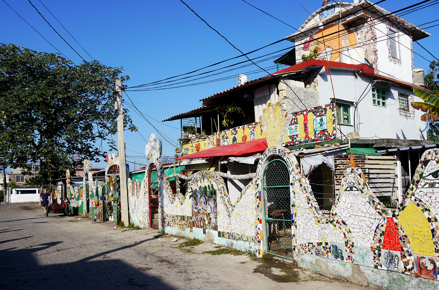 Street view of homes covered in mosaic tiles.
