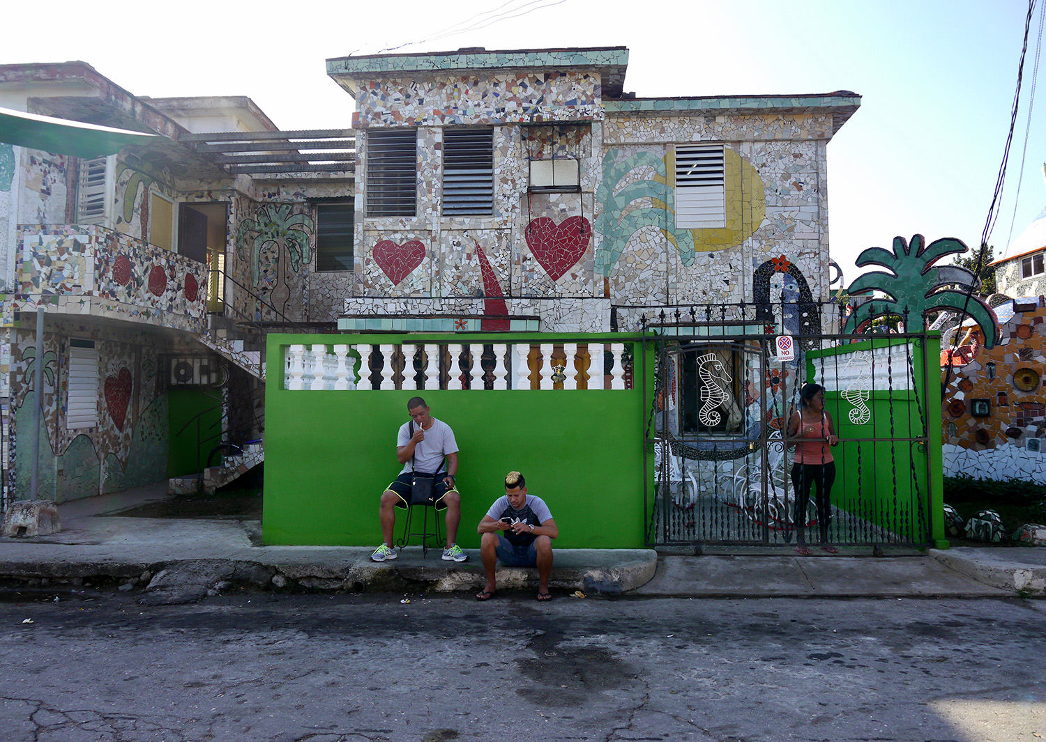 Three people wait outside a home decorated in mosaic tiles.