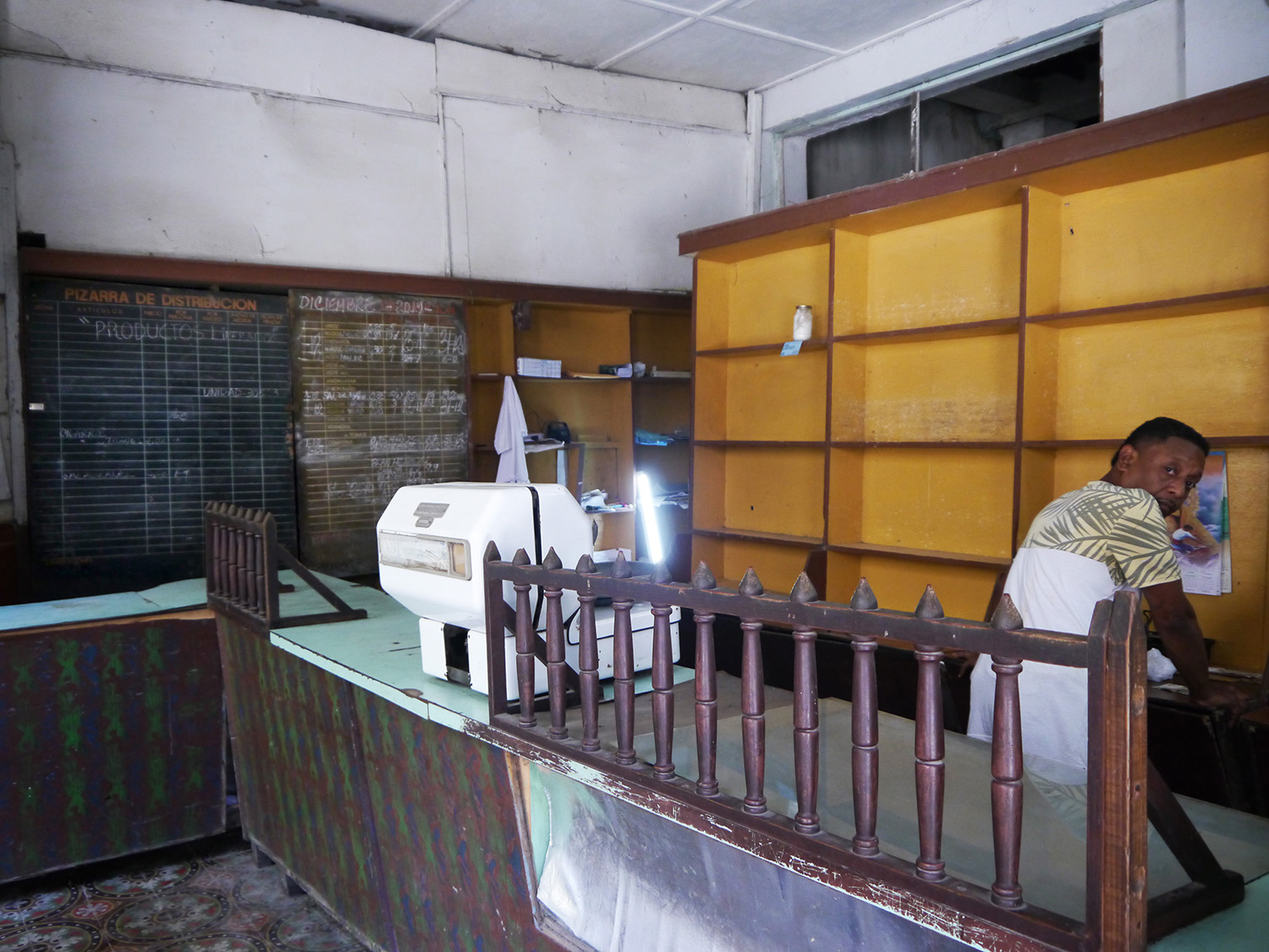 Man sits in front of empty shelves at a government store.