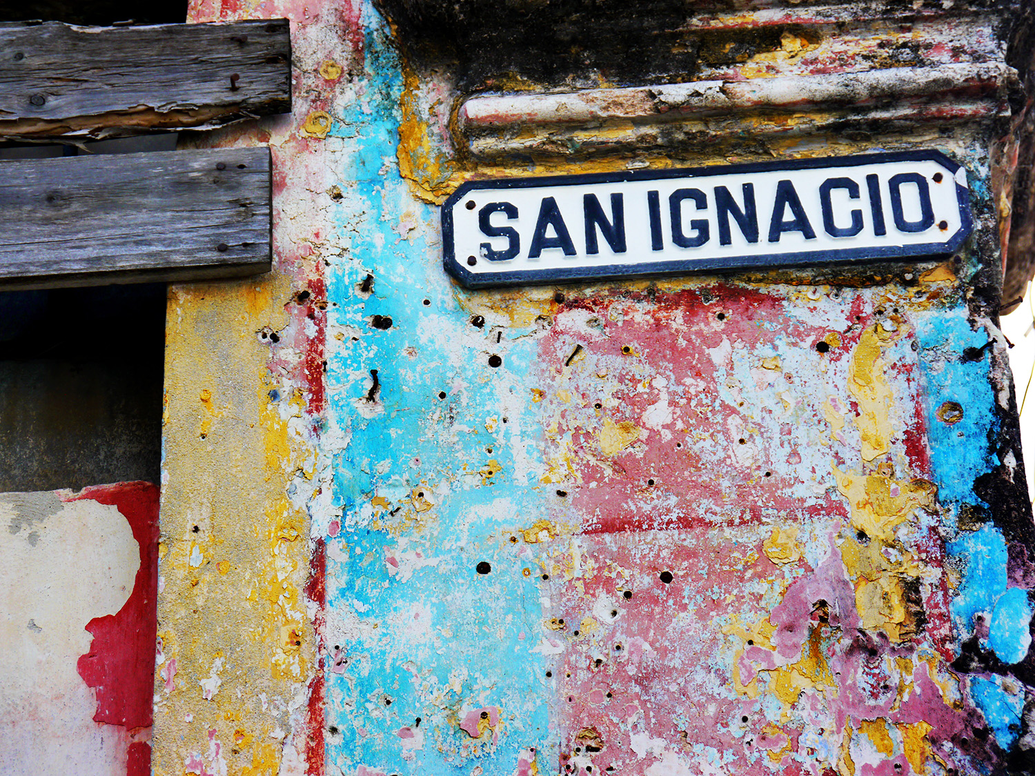A street sign on a colorful old building.