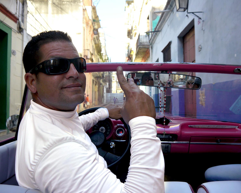 Cuban driver in a 1950s pink car.