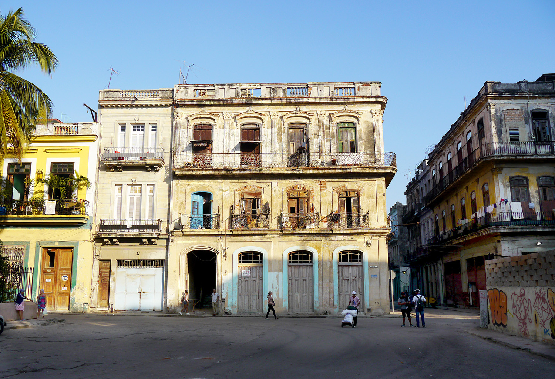 People work and talk in front of a rundown building in Havana.