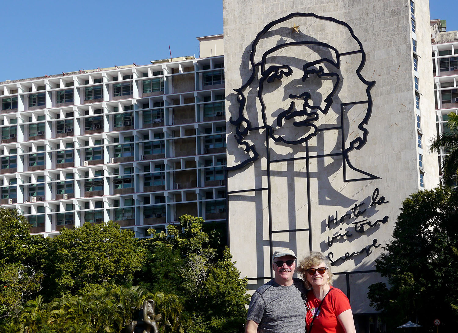 A couple poses in front of building with the image of Che Guevara.