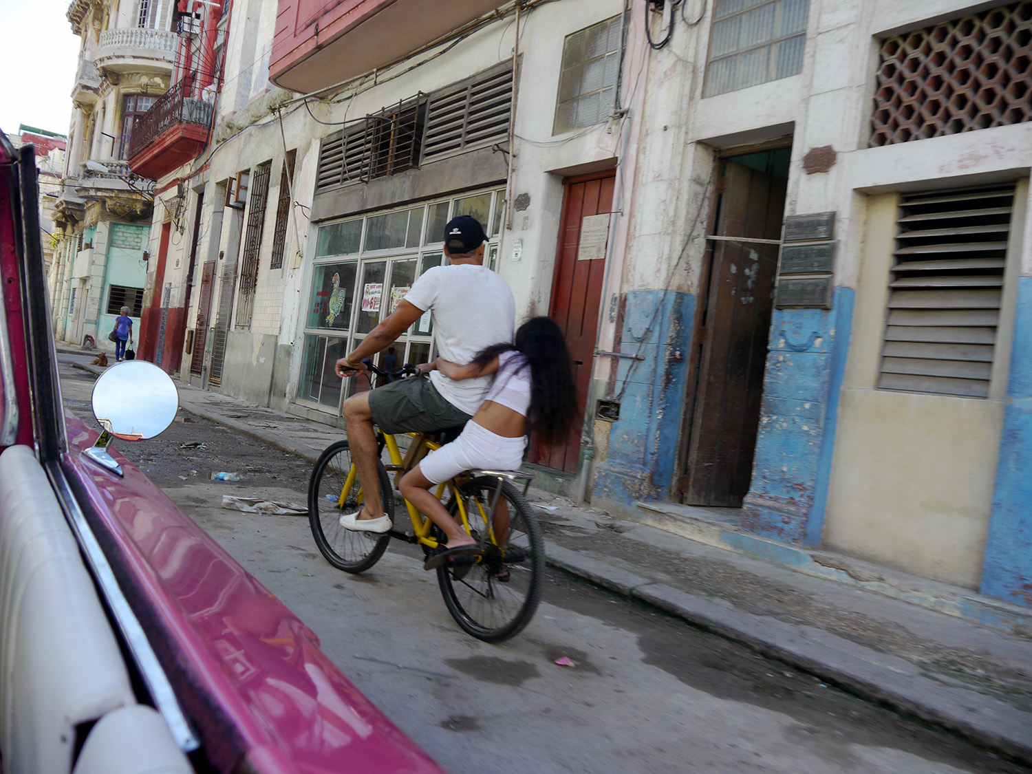 A woman hugs the back of a man on a bicycle in Havana.
