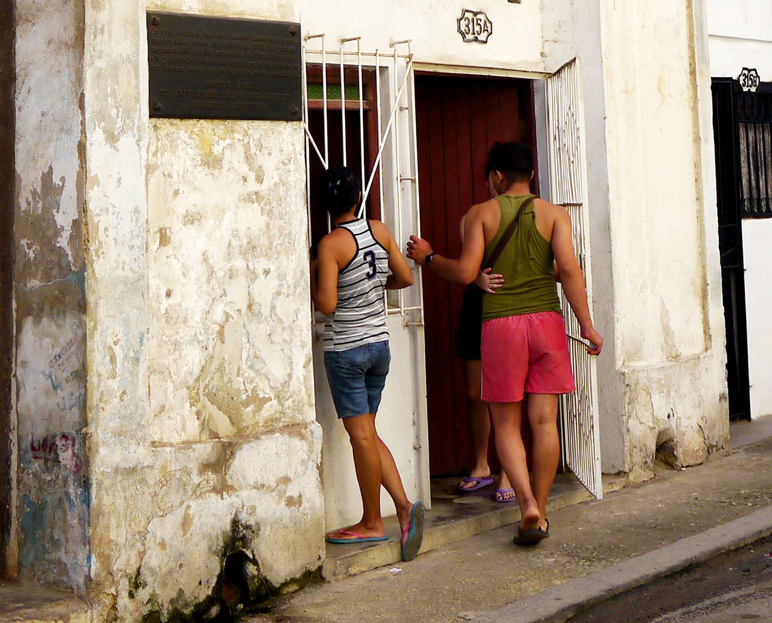 A man is greeted by the arms of a woman in a doorway in Havana.