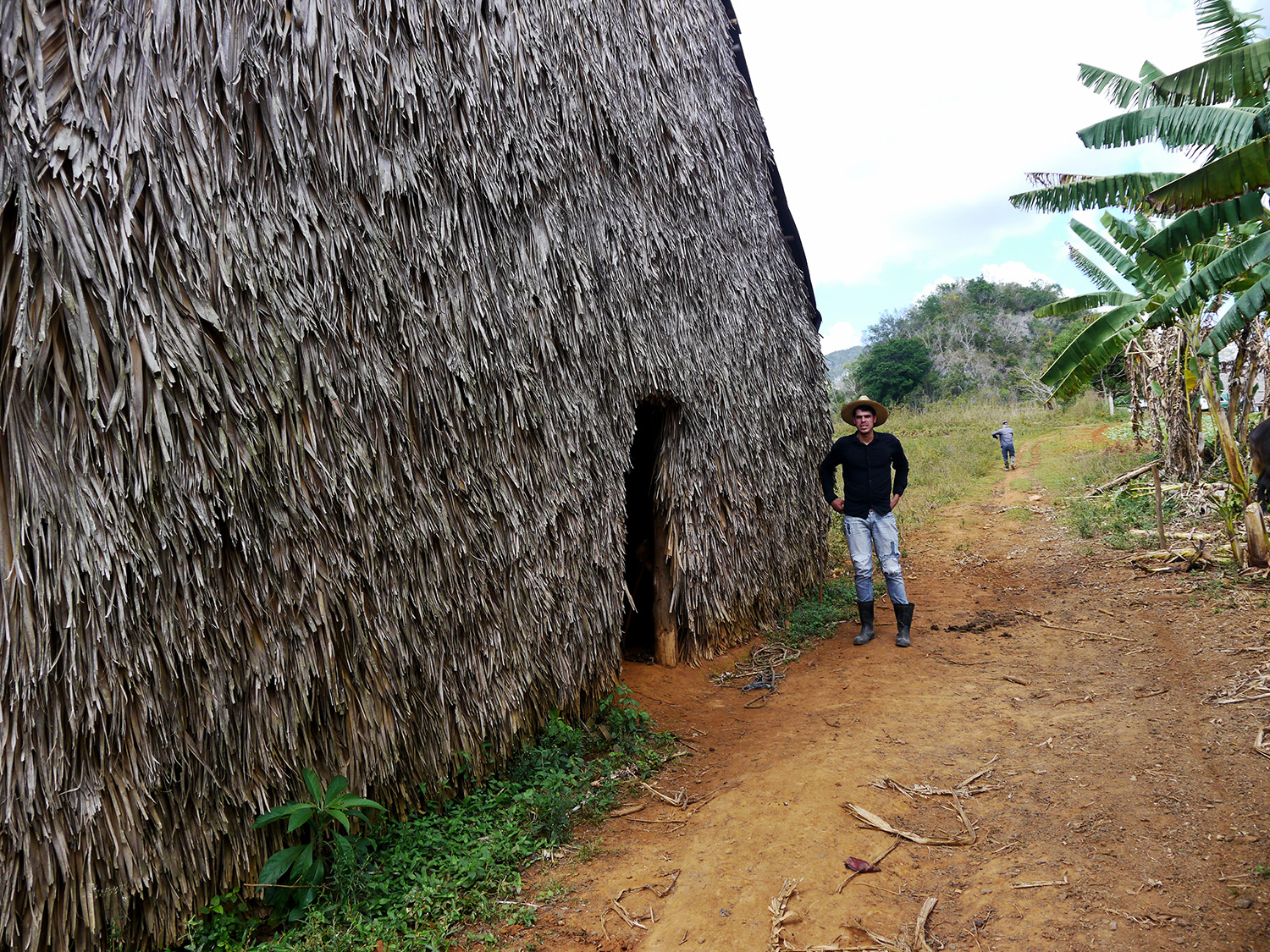 Farmer stands next to a thatched building.