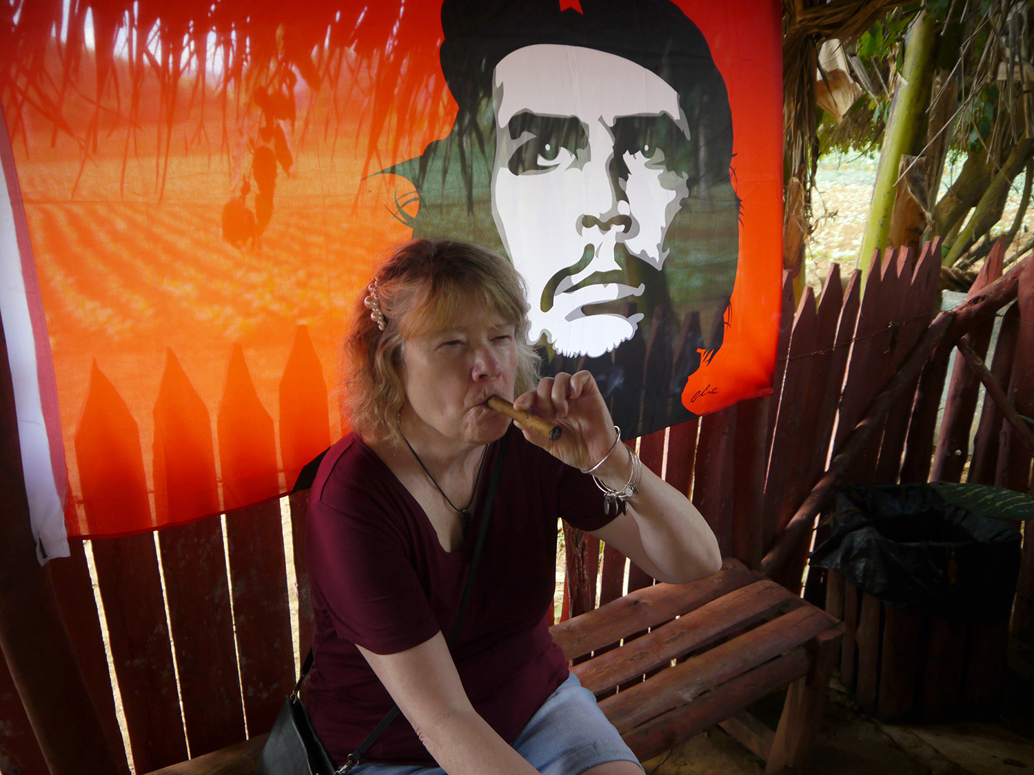 Tricia takes a drag on a cigar in front of a Che Guevara banner.