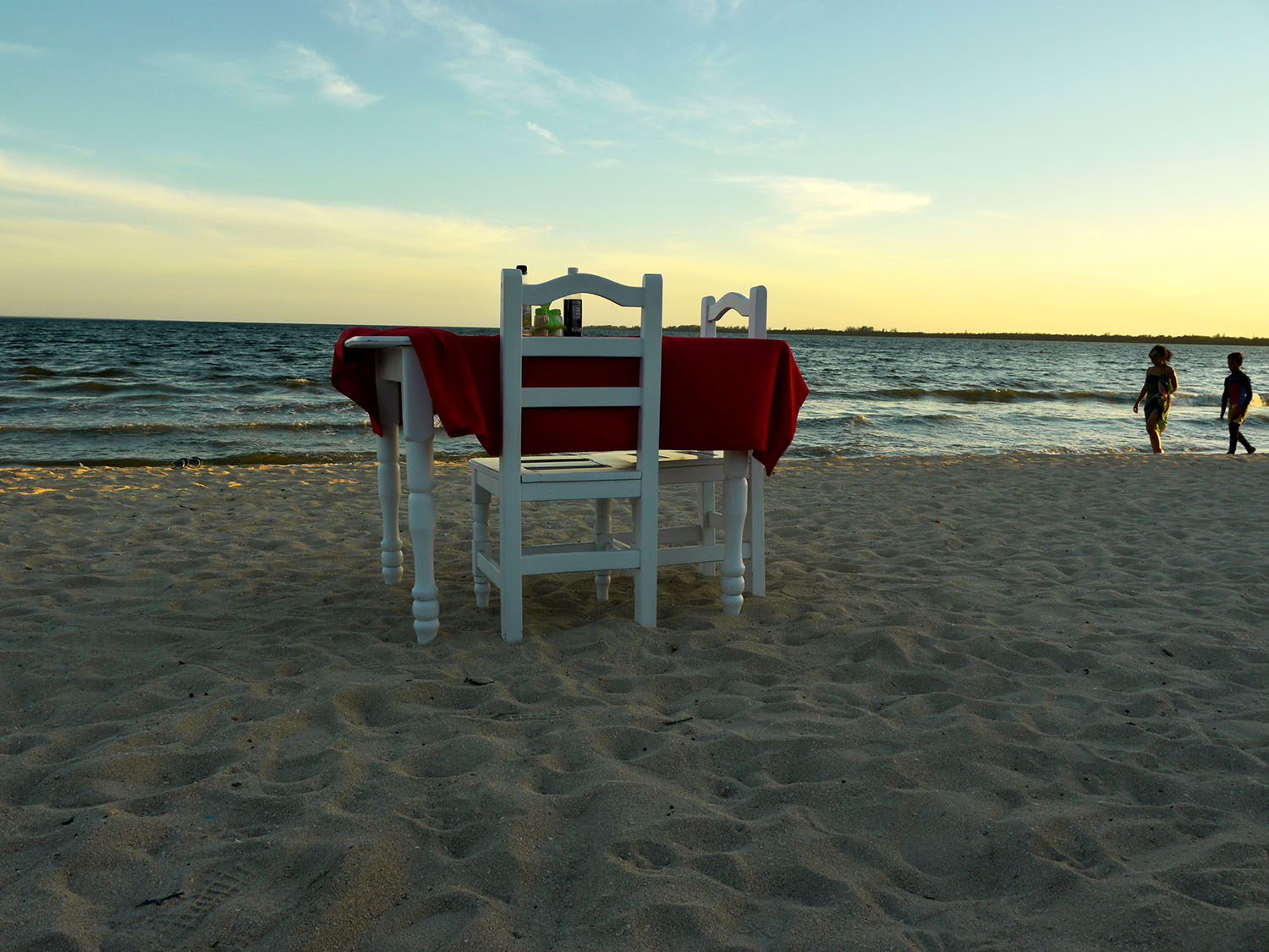 A dinner table in the sand.