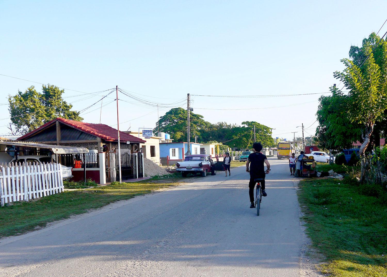 A man rides a bike on a quiet street.