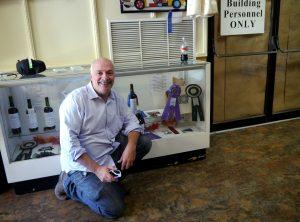 Mark posing before a wine award case